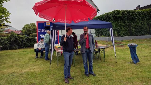Thomas Oppermann hält einen Schirm über Uwe Speit
